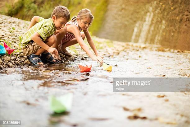 Niño y niña jugando papel paseos en barco por el río