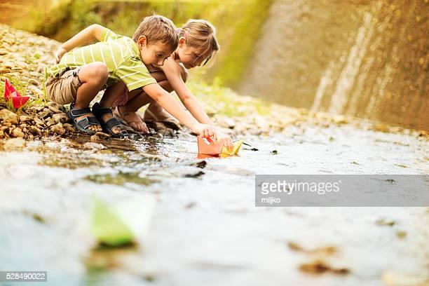 Jungen und Mädchen spielen mit Papier-Boote auf dem Fluss