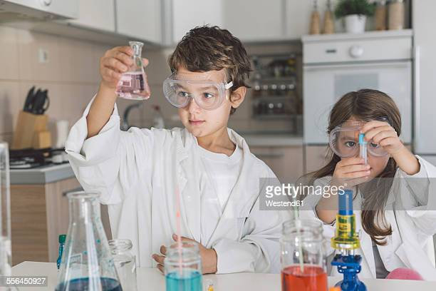 Boy and girl playing science experiments at home
