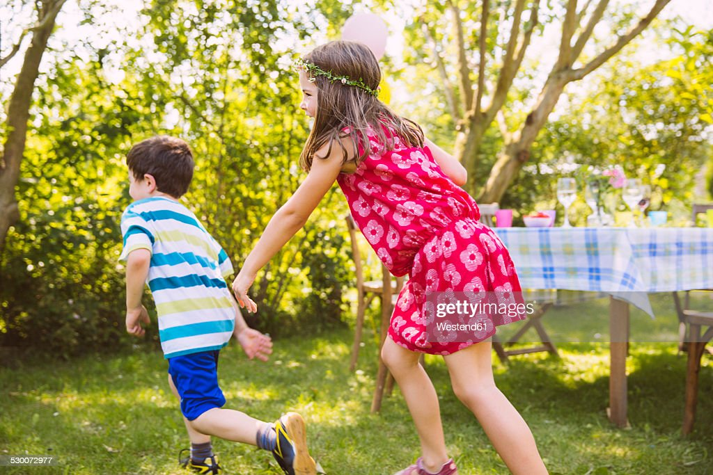Boy and girl playing tag in garden : Stock Photo