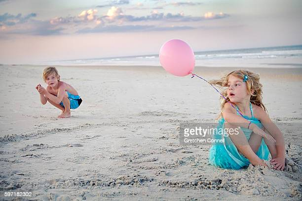Boy and girl playing with a pink balloon on the beach