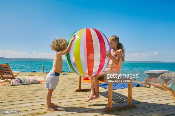 Boy and girl playing with beach ball on houseboat sun deck, Kraalbaai, South Africa