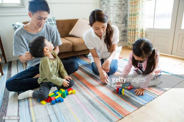 Boy and girl playing with blocks with parents on floor