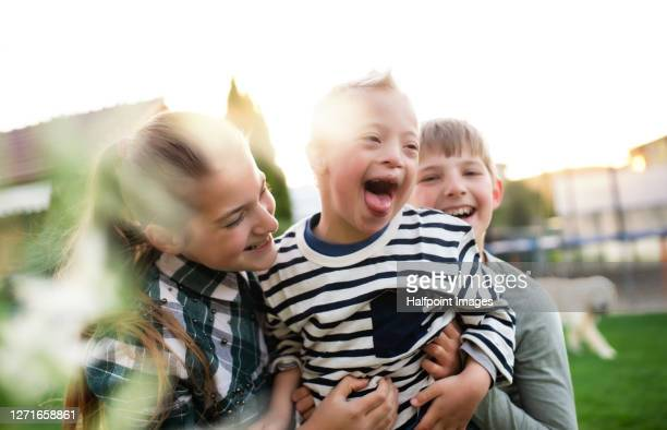 boy and girl playing with down syndrome brother outdoors in garden. - sibling stock pictures, royalty-free photos & images