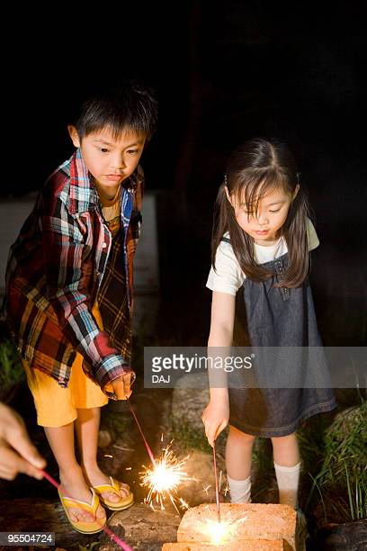 Boy and girl playing with firework
