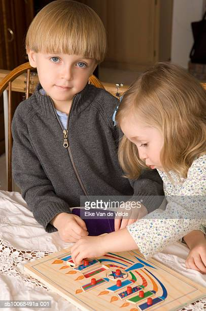 Boy and girl (4-6) playing with menorah puzzle, indoors