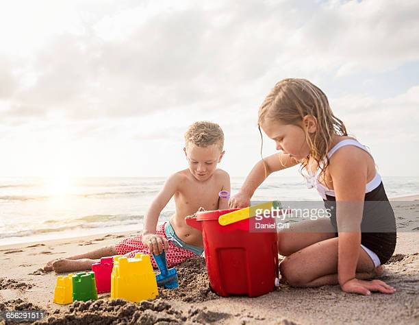 Boy (6-7) and girl (4-5) playing with sand on beach