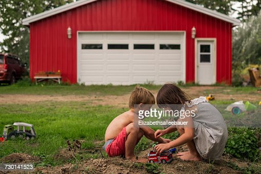 Boy and girl playing with toy cars