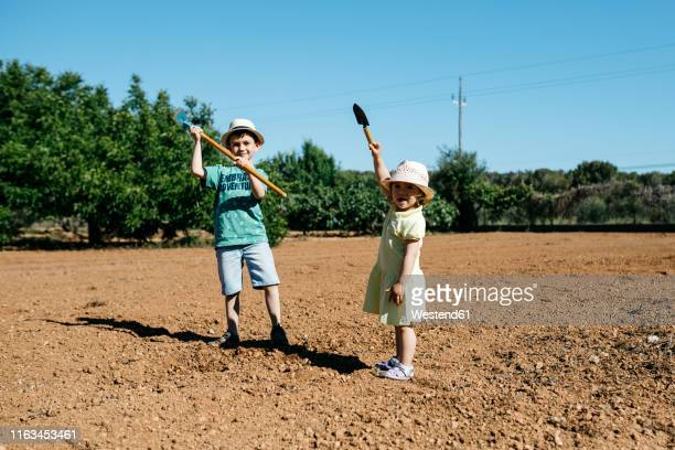 Boy and girl plowing the ground
