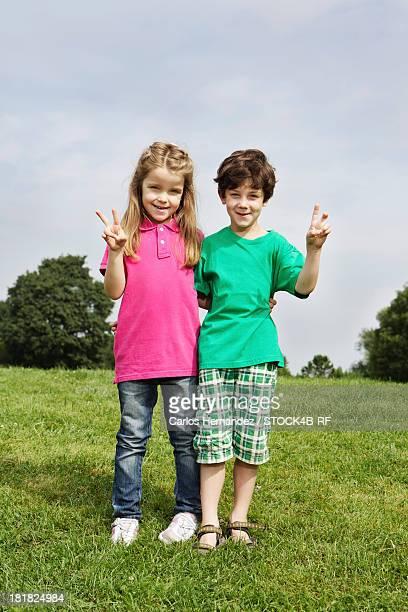 Boy and girl posing on meadow
