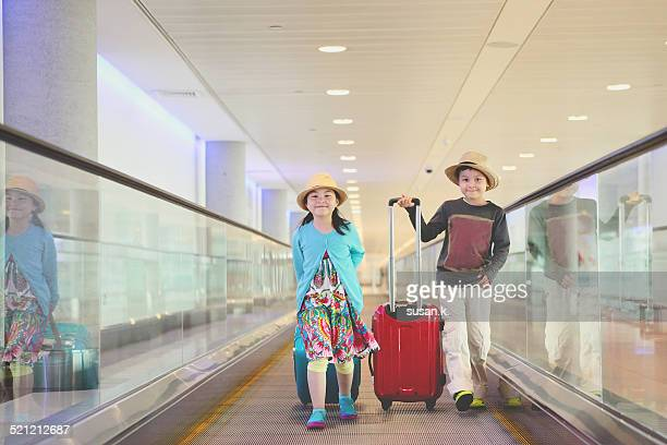 Boy and girl pulling suitcase at the airport