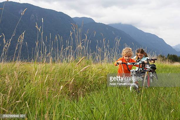 boy and girl (5-8 years) pushing mountain bikes through long grass - 6 7 years stock pictures, royalty-free photos & images