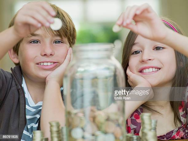 Boy and girl putting coins in jar