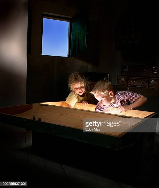 boy and girl (4-6) reaching inside illuminated large box - girl chest stock photos and pictures