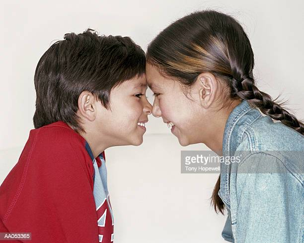 Boy and girl (6-11) rubbing noses, smiling, side view
