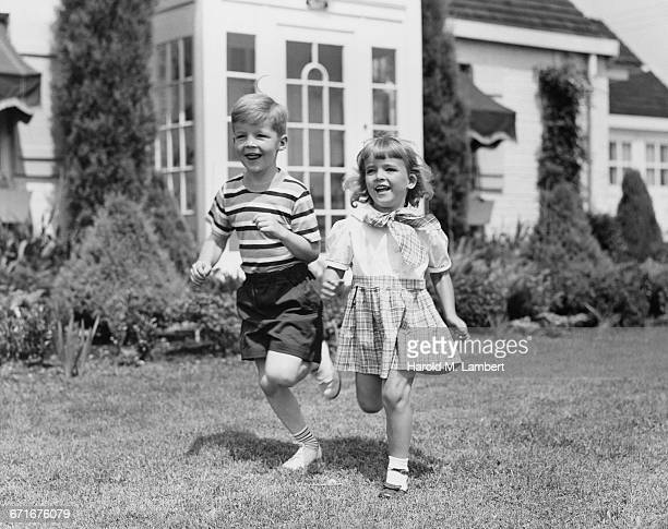 boy and girl running in garden - {{ collectponotification.cta }} foto e immagini stock