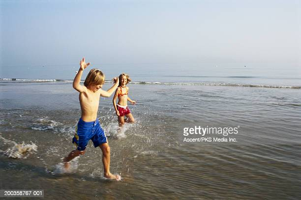 Boy and girl (10-12) running in water at beach, laughing