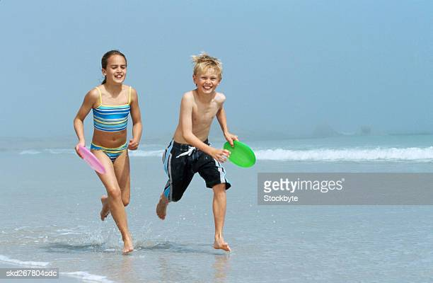 boy and girl running on beach and carrying plastic discs (10-11) - 10 11 jahre stock-fotos und bilder