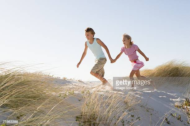 Boy and girl running on sand dune
