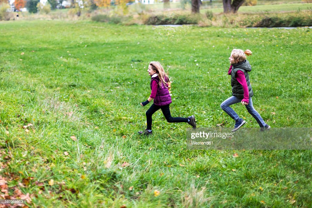 Boy and girl running over a meadow : Stock Photo