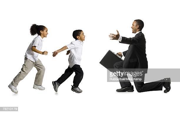 Boy and girl running toward kneeling businessman