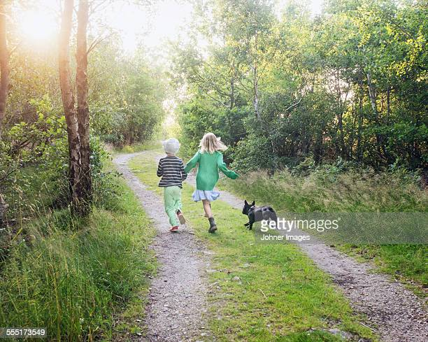 Boy and girl running with dog