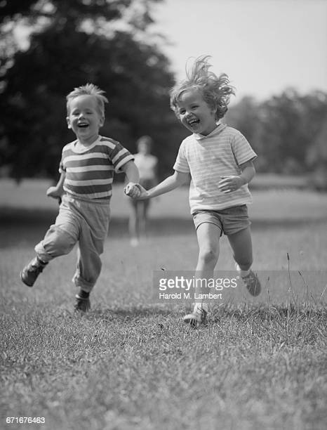 """  boy and girl running with holding hands, smiling "" - {{relatedsearchurl(carousel.phrase)}} stock pictures, royalty-free photos & images"