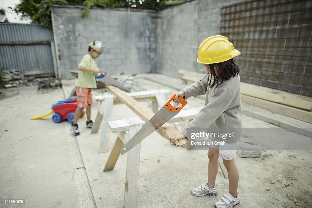 Boy and girl sawing wood : Stock Photo