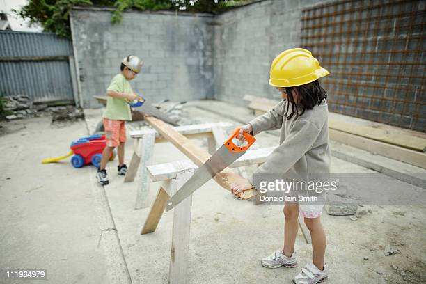 Boy and girl sawing wood