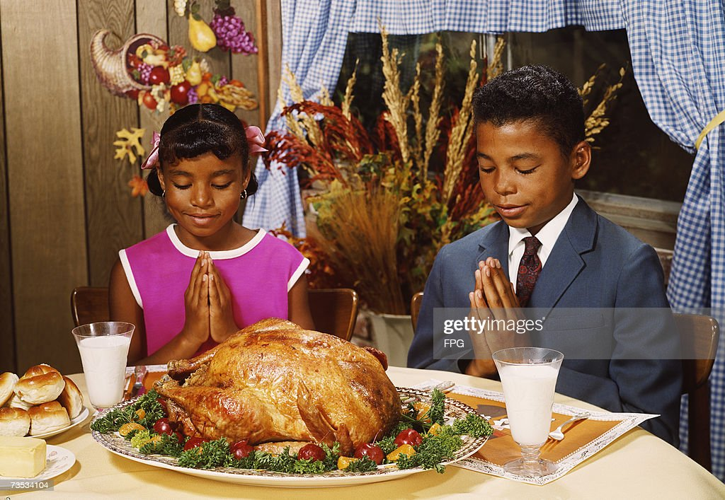 A boy and girl saying grace before a roast turkey dinner, circa 1970.