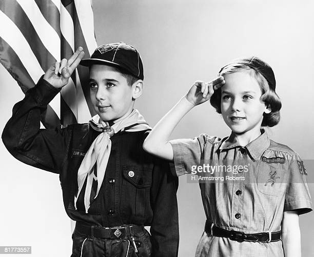 Boy and girl scouts saluting, American flag in background.