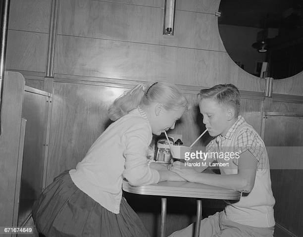boy and girl sharing a drink with straws in caf? - {{relatedsearchurl(carousel.phrase)}} stock pictures, royalty-free photos & images