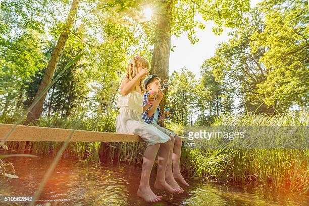 boy and girl sitting above small stream blowing soap bubbles - spring flowing water stock pictures, royalty-free photos & images