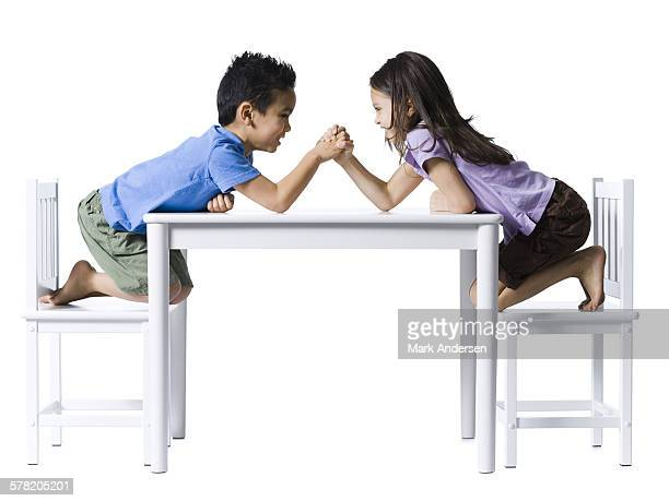 Boy and girl sitting at table arm wrestling