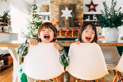 Boy and girl sitting at the dining table messing about at Christmas - gettyimageskorea