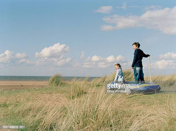 Boy and girl (8-14) sitting in inflatable boat on grass