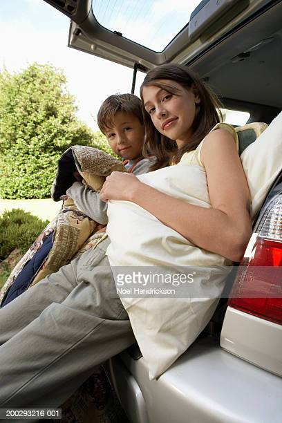 Boy (7-9 years) and girl (13-15 years) sitting in open boot of car, holding sleeping bag and pillow, portrait