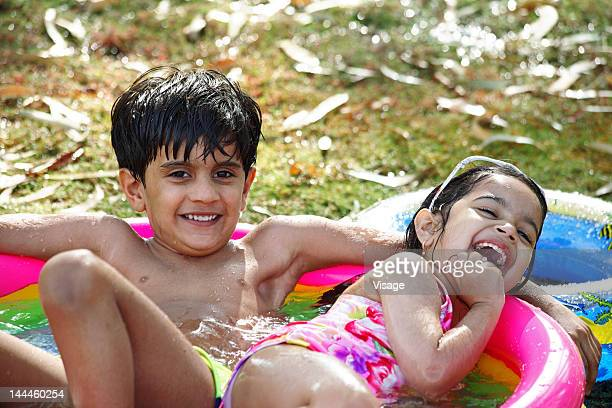 Boy and girl sitting in paddling pool, Laughing