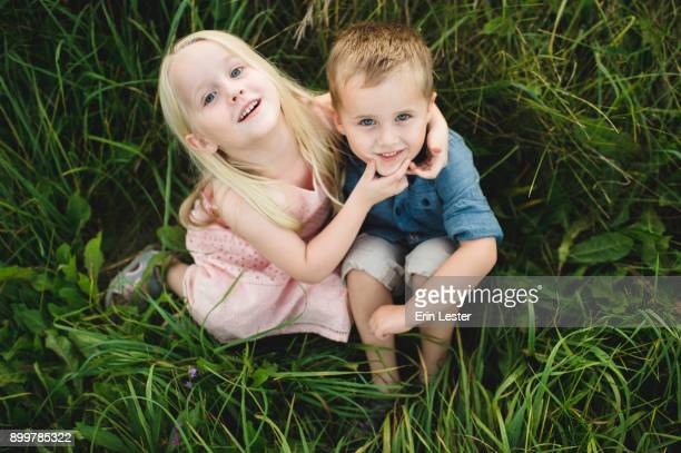 boy and girl sitting in tall grass together, looking up at camera - bruder stock-fotos und bilder