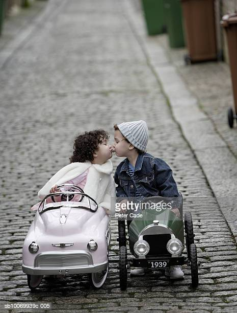 Boy and girl (2-3) sitting in toy car and kissing, side view
