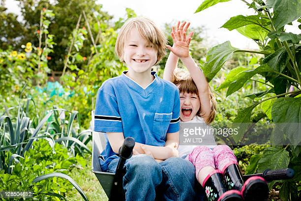 boy and girl sitting in wheelbarrow - children only stock pictures, royalty-free photos & images