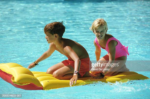 Boy (8-9) and girl (4-7) sitting on airbed in swimming pool