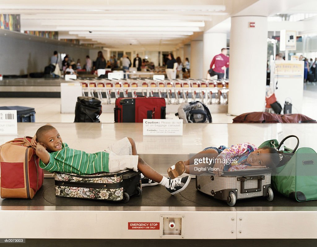 Boy and Girl Sitting on Baggage Conveyor Belt : Stock Photo