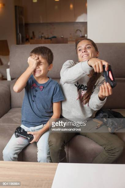 boy and girl sitting on couch playing video games - losing virginity stock pictures, royalty-free photos & images