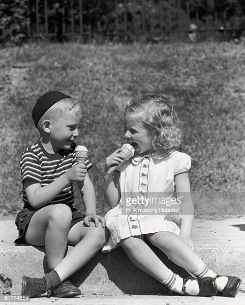 Boy and girl sitting on curb, eating ice cream cones.