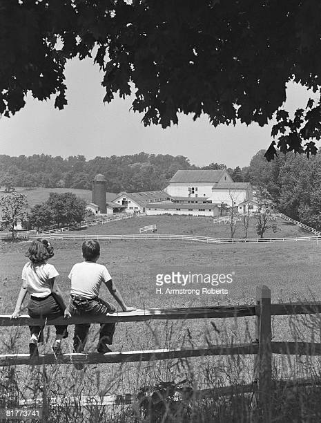 Boy and girl sitting on fence, overlooking farm fields.