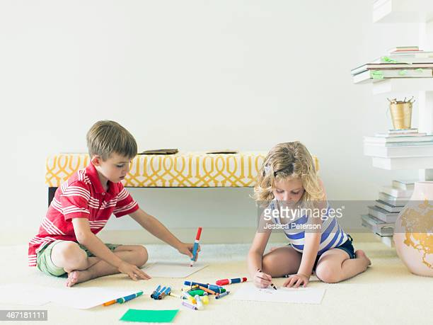 Boy and girl (4-5, 6-7) sitting on floor and drawing
