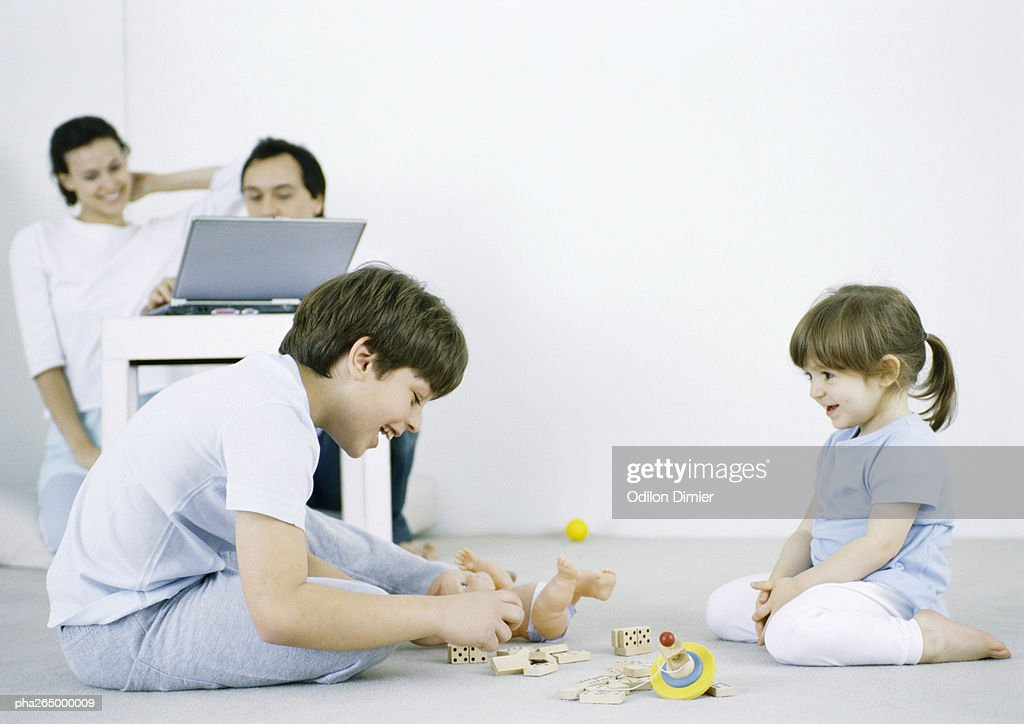 Boy and girl sitting on floor playing, man and woman using laptop in background : Stockfoto