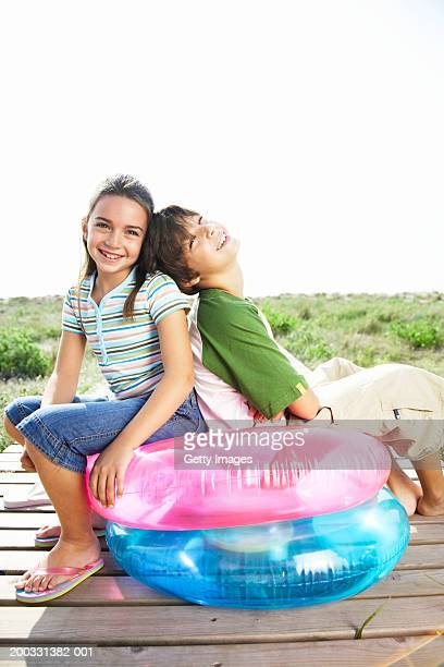 Boy and girl (8-10) sitting on inflatable rings on beach boardwalk
