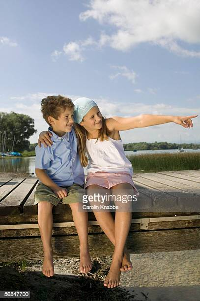 Boy and girl (6-9) sitting on jetty
